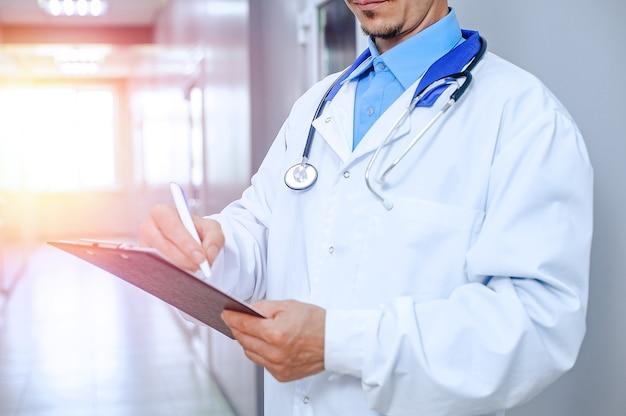 男性医師の笑顔を閉じます。病院のホールで聴診器で若い医者 Premium写真