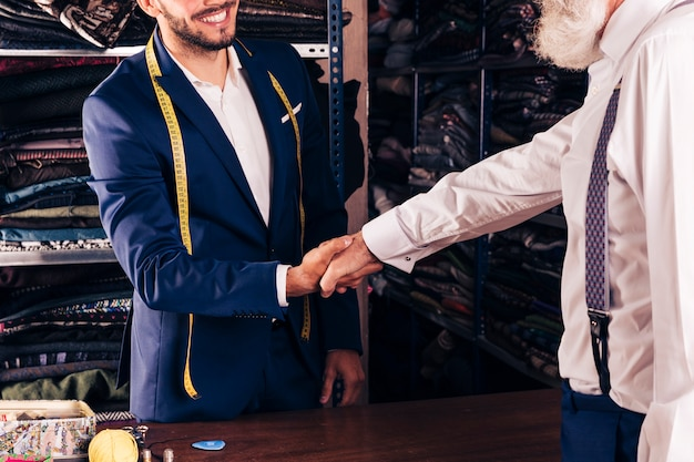 Close-up of smiling male tailor shaking hand with senior customer Free Photo