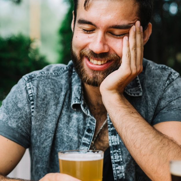 Close-up of a smiling man holding glass of beer Free Photo