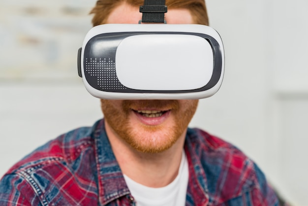 Close-up of a smiling man wearing virtual reality glasses Free Photo