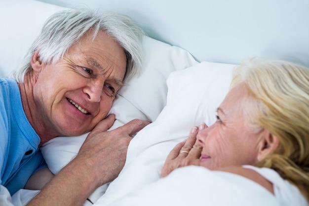 Close-up of smiling senior couple sleeping on bed Premium Photo