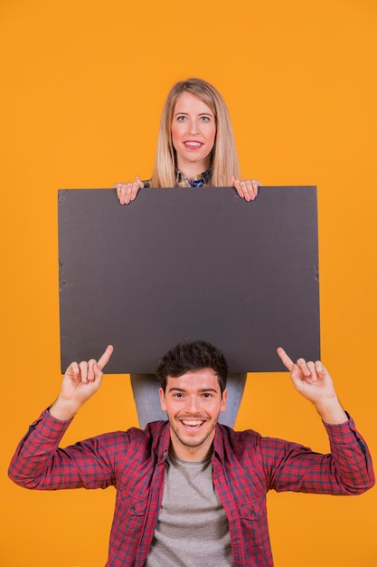Close-up of a smiling young couple showing blank placard against an orange background Free Photo