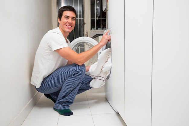Close-up of a smiling young man putting clothes in the washing machine Free Photo