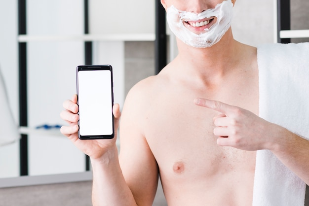 Close-up of a smiling young shirtless man with shaving foam on his face pointing finger toward mobile phone in hand Free Photo