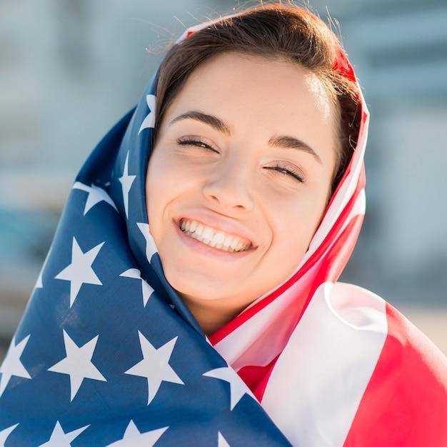 Макро улыбается молодая женщина, держащая большой флаг сша Бесплатные Фотографии