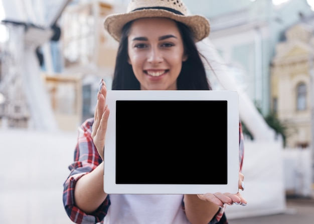 Close-up of smiling young woman showing digital tablet Free Photo