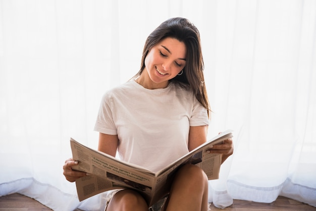 Close-up of a smiling young woman sitting in front of white curtain reading the newspaper Free Photo
