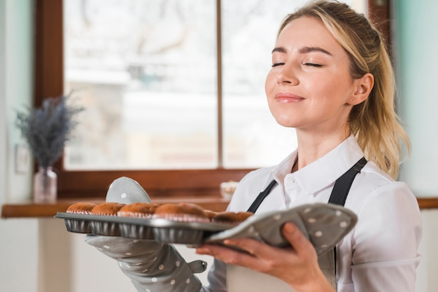 Close-up of a smiling young woman smelling the fresh baked muffins Free Photo