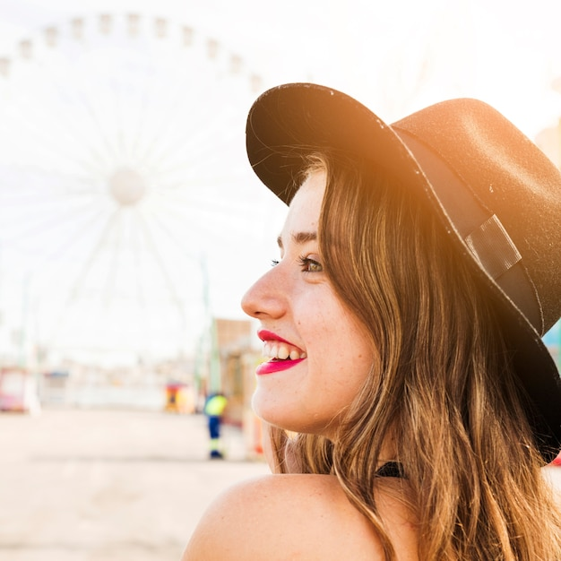 Close-up of smiling young woman with black hat on her head Free Photo