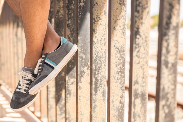 Close-up sneakers with metal fence Free Photo