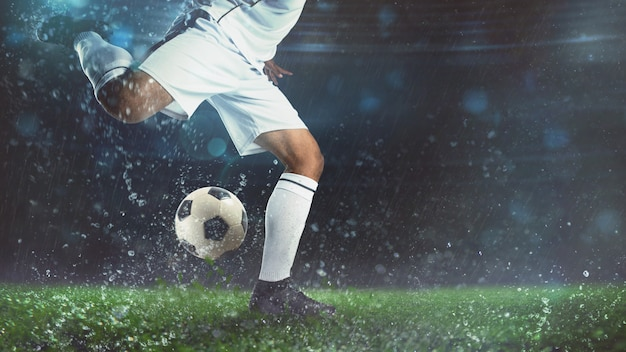 Close up of a soccer scene at night match with player in a white uniform kicking the ball with power Premium Photo
