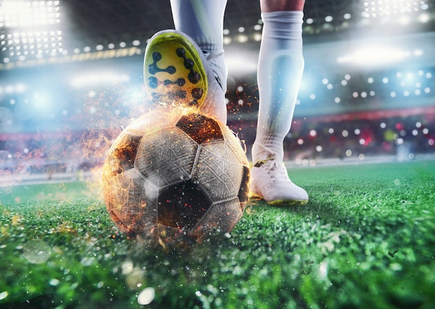Close up of a soccer striker ready to kicks the fiery ball at the stadium Premium Photo