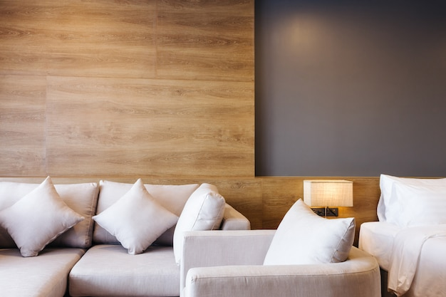 Close-up of sofa and white pillow on bed decoration with light lamp in hotel bedroom interior. Premium Photo
