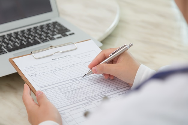 Close-up of specialist filling out a form Free Photo