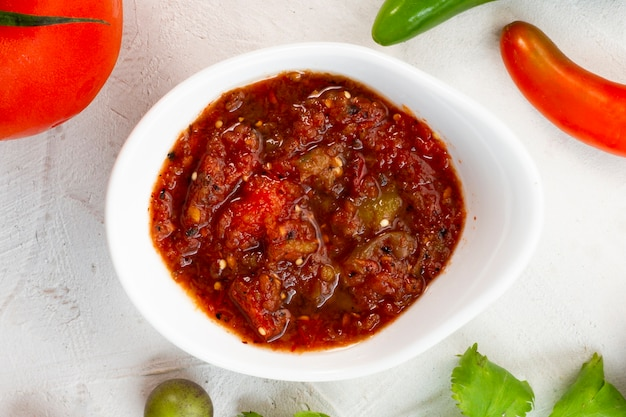 Close-up spicy salsa with white background Free Photo