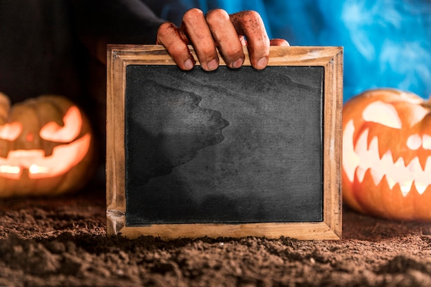 Close-up spooky hand holding blackboard Free Photo