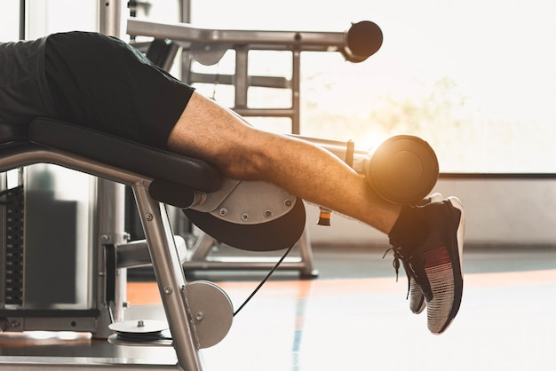 Close up of sport man stretching and lifting weight by two legs when facing down for stretching Premium Photo