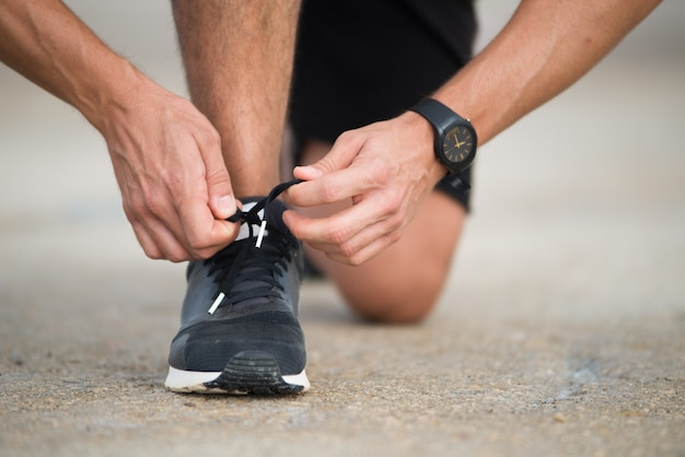 Close-up of sportsman tying sneakers Free Photo