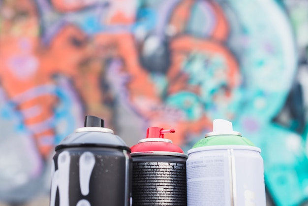 Close-up of spray cans in front of blur graffiti wall Free Photo
