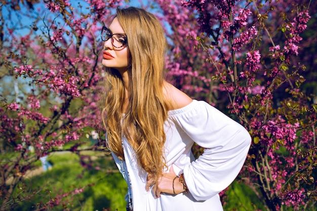 Close up primavera estate ritratto di splendida giovane donna con capelli lunghi naturali incredibili e bellezza viso, indossando occhiali trasparenti, colori solari. Foto Gratuite