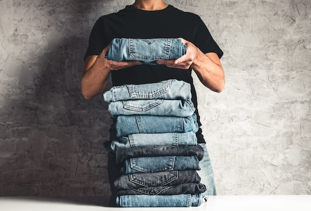 Close up stack of folded denim blue jeans in hand over gray wall background, copy space Premium Photo