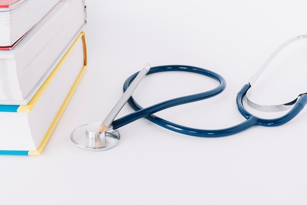 Close-up of stacked books and stethoscope on white backdrop Free Photo