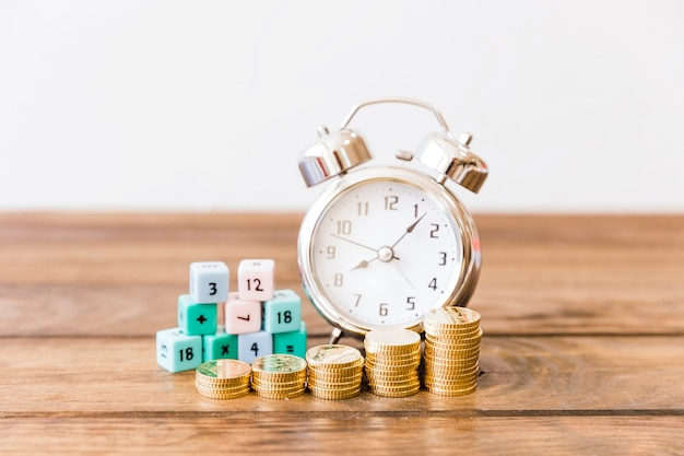 Close-up of stacked coins in front of alarm clock and math blocks on wooden desk Free Photo