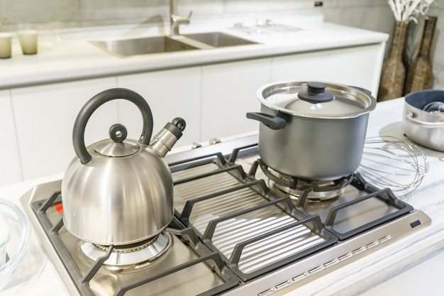 Close-up of stainless steel cooking pot and kettle boiling on gas stove in home kitchen Premium Photo