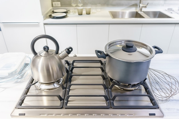 Close-up of stainless steel cooking pot and kettle boiling on gas stove in kitchen Premium Photo