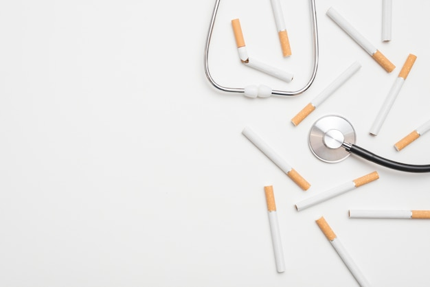 Close-up of stethoscope and cigarettes suggesting a stop smoking theme Free Photo