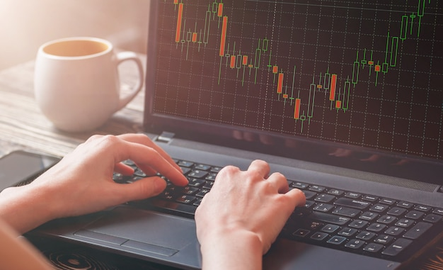 Close-up of a stock market broker's female hand analyzing graph on laptop. Premium Photo