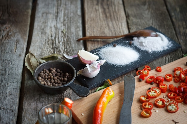 Close-up of stone stand with heaps of salt, sugar, garlic, allspice, bay leaf next to a board with chopped chili peppers on an old wooden surface Premium Photo