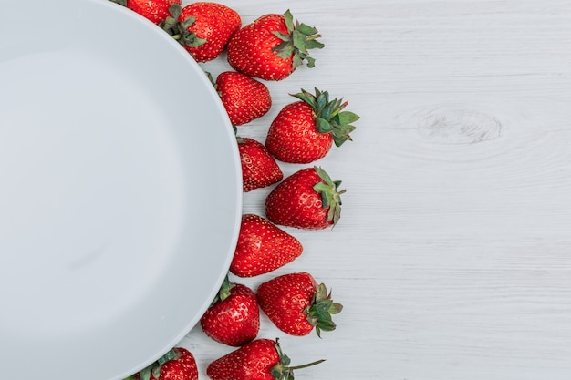 Close-up strawberries with empty plate on white wooden background. horizontal copy space for text Free Photo