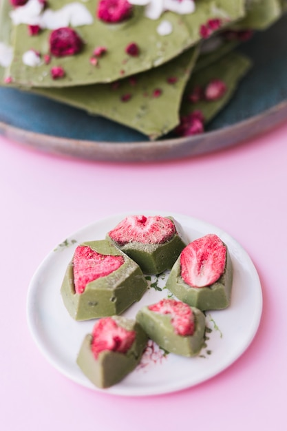 Close-up of strawberry with green chocolate dessert on white plate over pink surface Free Photo