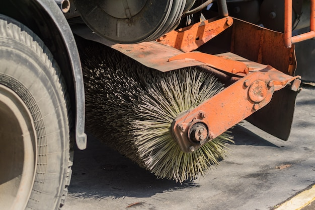 Close up of street cleaning sweeper machine washes the asphalt road Premium Photo