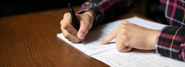 Крупным планом руки студента записывать ноты на уроке в школе Premium Фотографии