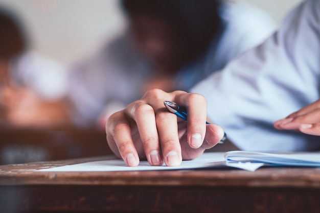 Close-up to student holding pencil and writing final exam Premium Photo