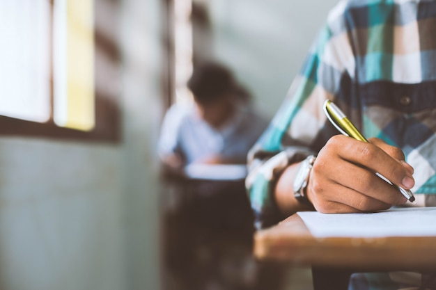 Close up students writing and reading exam answer sheets exercises in classroom of school with stress. Premium Photo