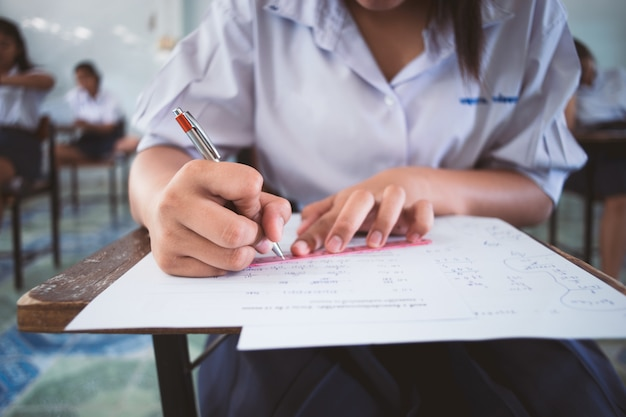 Close up students writing and reading exam answer sheets exercises in classroom of school Premium Photo