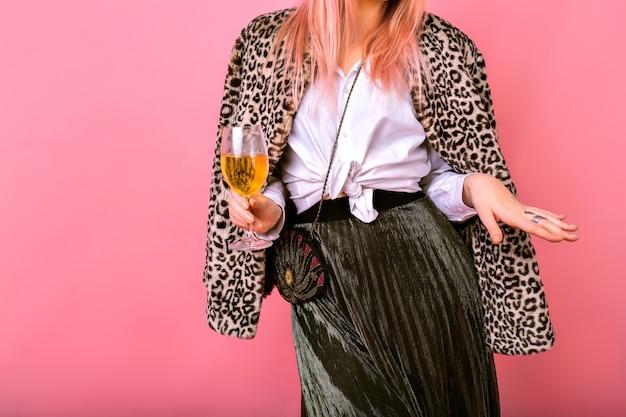 Крупным планом детали моды студии, элегантная молодая женщина в стильном вечернем наряде, классическая белая рубашка, сверкающая юбка и миниатюрная винтажная сумка, меховое леопардовое пальто, пьет шампанское и танцует. Бесплатные Фотографии