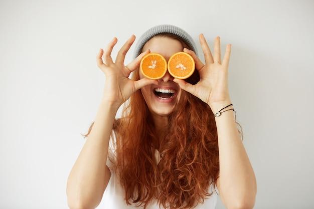 Close up ritratto in studio di giovane donna sorridente che tiene metà delle arance ai suoi occhi Foto Gratuite