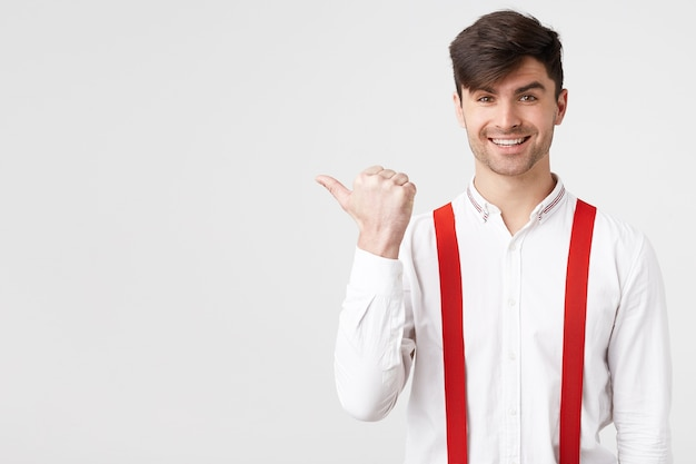 Close up of stylish attractive guy in white shirt and red suspender pointing aside with pleasant smile Free Photo