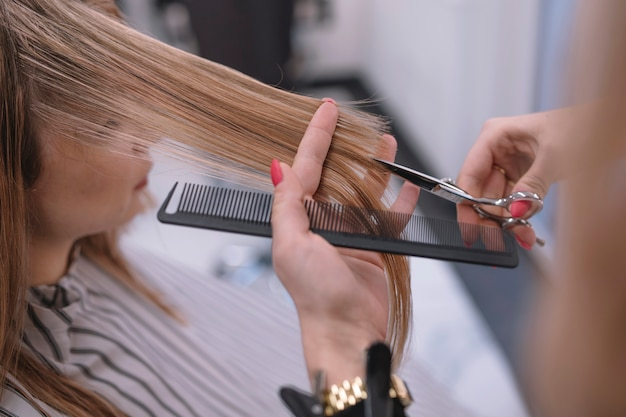 Close-up of stylist cutting hair ends Free Photo