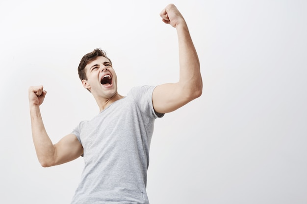 Close up of successful young caucasian male sportsman screaming yes and raising clenched fists in the air, feeling excited. people, success, triumph, victory, winning and celebration. Free Photo