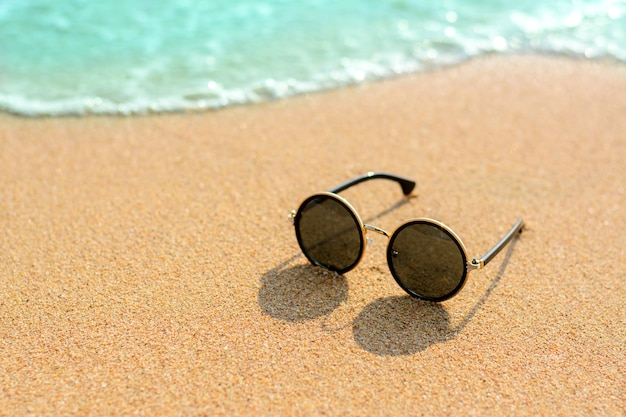05380364ce6c Close up sunglasses on the beach and blur blue sea background Photo ...