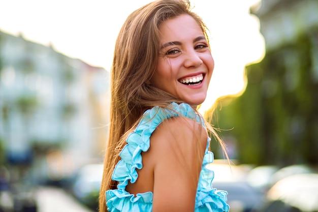 Закройте солнечный портрет красивой великолепной женщины с естественным макияжем и большой удивительной улыбкой, смотрящей в камеру, ярким солнечным светом, позитивным настроением. Бесплатные Фотографии