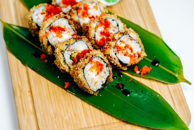 Close up of sushi rolls garnished with red tobiko served on leaves Free Photo