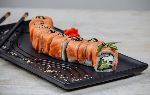 Close up of sushi rolls set covered in salmon with cucumber and cream Free Photo