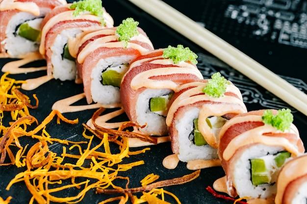 Chiuda in su dei rotoli di sushi con il cetriolo coperto di tonno e guarnito con salsa piccante e tobiko verde Foto Gratuite