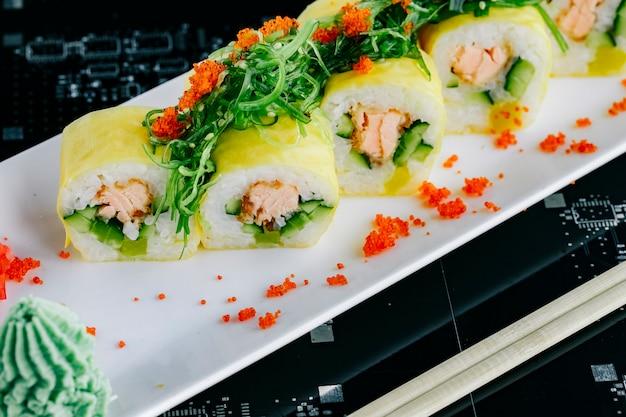 Primo piano di involtini di sushi con salmone fritto e cetriolo condita con alghe e tobiko rosso Foto Gratuite